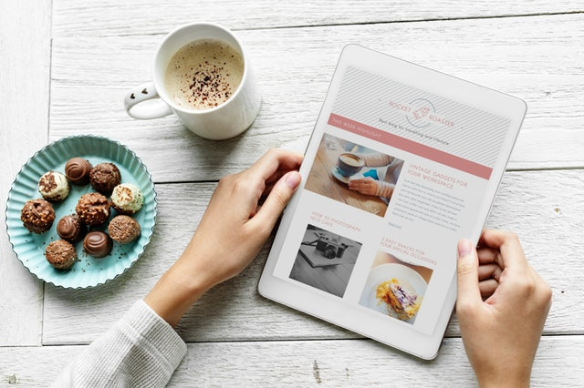 ruce držící tablet s otevřenými stránkami o jídlech