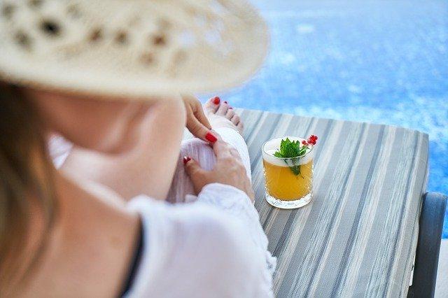 žena s drinkem sedící u bazénu